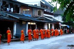 Les moines demandent l'aumône dans les petites rues à Luang Prabang